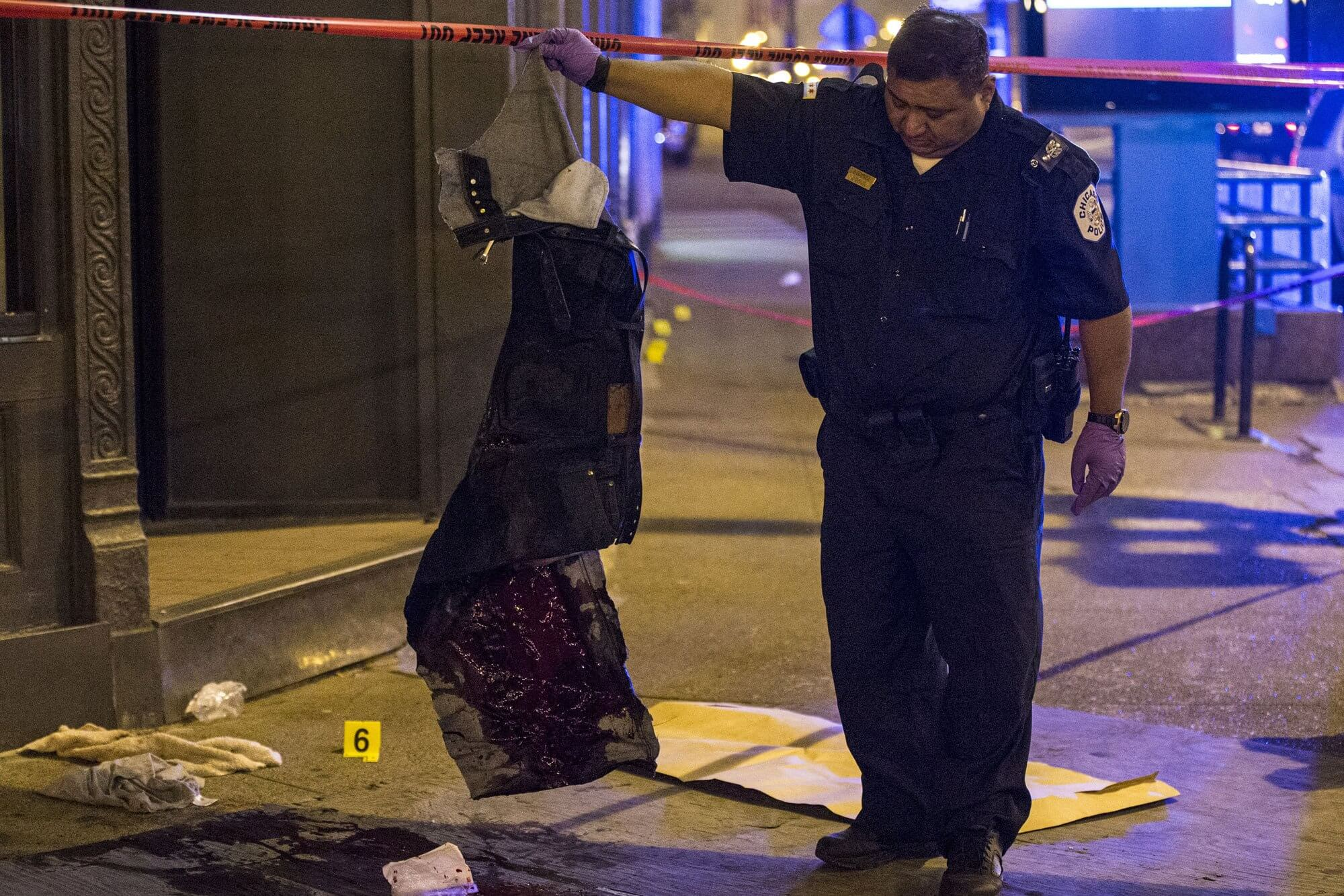 A police officer in Chicago, Illinois inspects bloody clothing belonging to a gunshot victim.