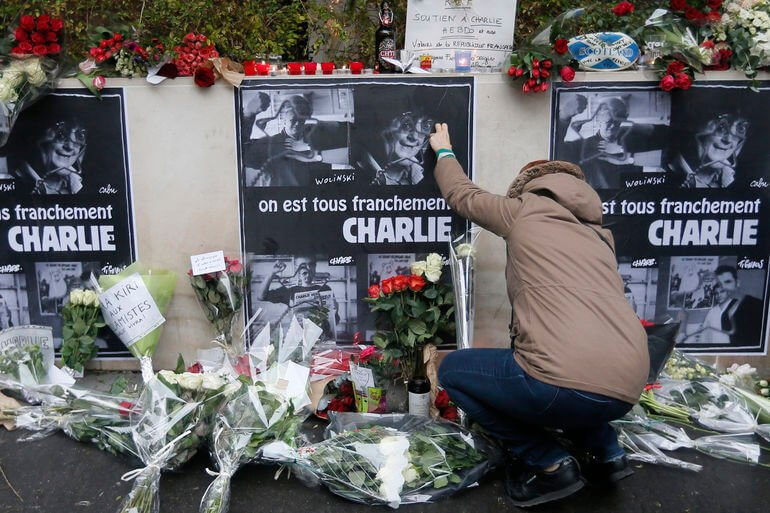 A mourner adds flowers to a Charlie Hebdo memorial as photographed in January 2015 by Gonzalo Fuentes via Reuters.