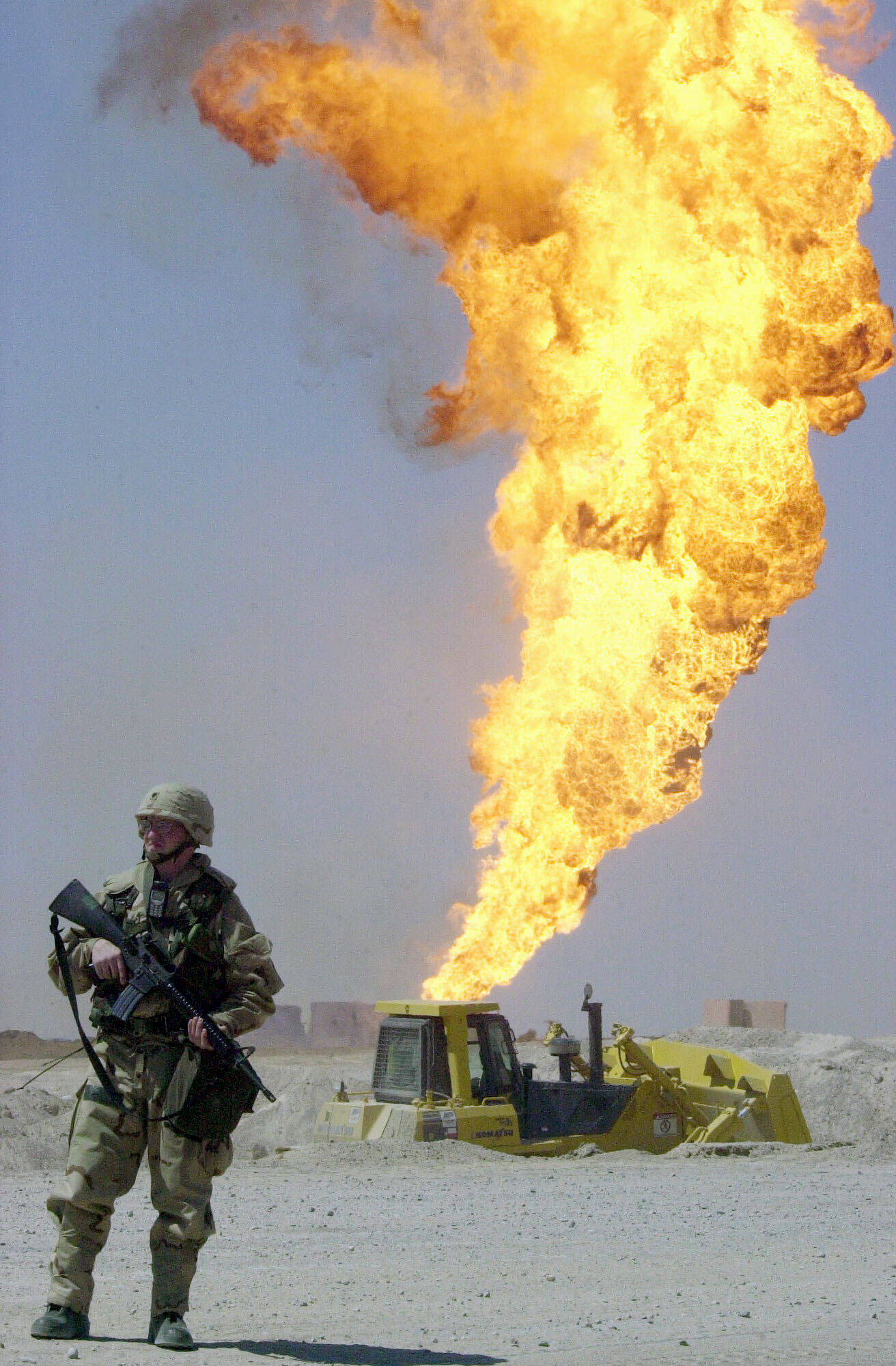 Soldier near burning oil well in Rumaylah oil field