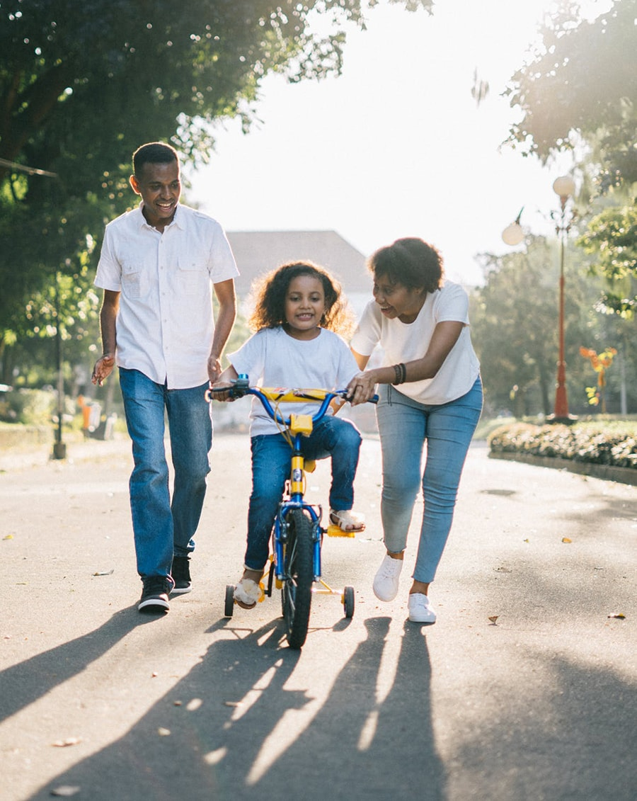 Mom and Dad teaching daughter to ride a bike