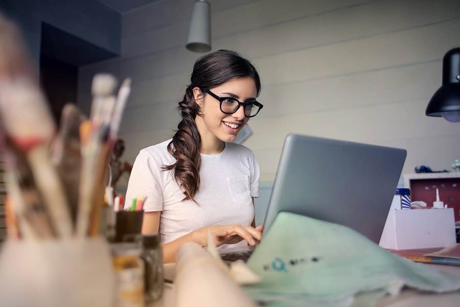Girl in glasses sitting at computer, smiling
