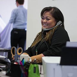Support specialist on phone smiling