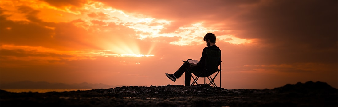 Man reading during a sunset.