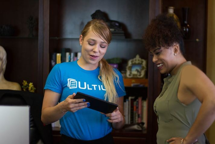 Ultius staff looking at a tablet and smiling.
